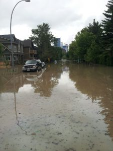 An image of the flood in the Sunnyside neighbourhood. The road is completely covered in muddy water.