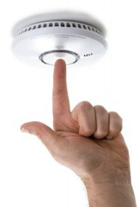 Close-up of a hand pressing a button on a smoke detector
