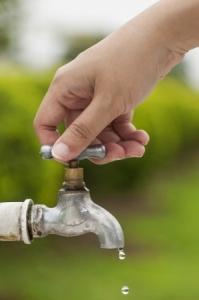 Close-up of a hand turning off an outdoor faucet