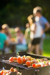 Group of friends enjoys a backyard barbecue, with grill in the foreground.