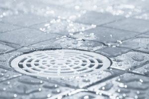 Close-up of a drain in a grey-tiled shower