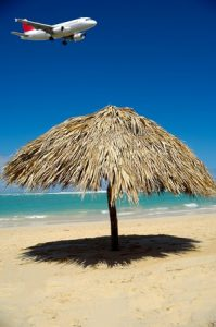 Thatched umbrella on a tropical beach, with a plane flying overhead