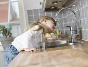 Little girl drinks water from kitchen tap.