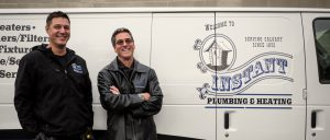 George Pinel, owner of Instant Plumbing, standing with his son in front of a company van