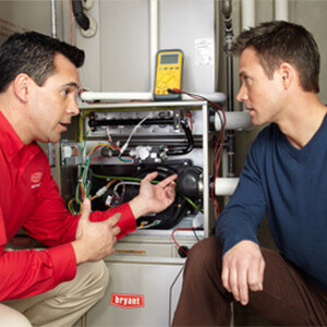 Repairperson and a homeowner, in front a furnace and a diagnostic tool, talking