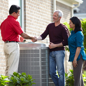 Outside a home, in front of an air conditioning unit, a repairperson shakes hands with the homeowners