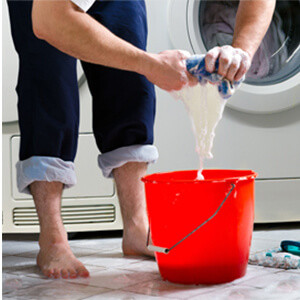 A person rings out a wet rag into a bucket, due to a leak in their laundry room