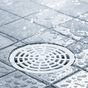 Drain in a grey-tiled shower