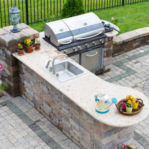 Elaborate outdoor backyard stone patio with a gas BBQ