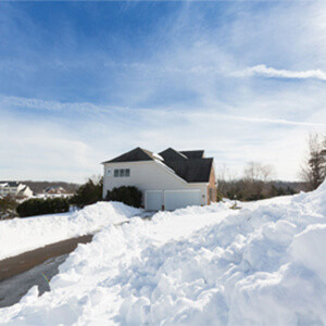 House with a double garage and a long driveway in winter, surrounded by piles of snow