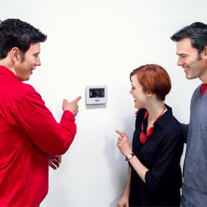 Technician explaining to homeowners about a home automation system, in front of a thermostat