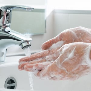 Person washing their hands in a bathroom sink