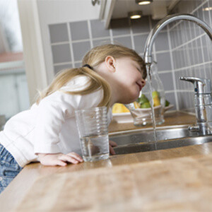 A young girl drinking water from a kitchen tap