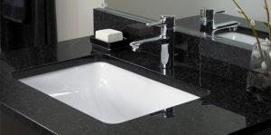 Modern stainless steel faucet on a black granite bathroom vanity