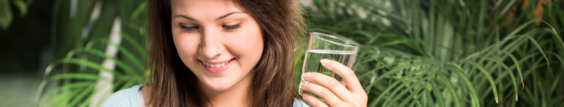 Woman smiling and holding a glass of water