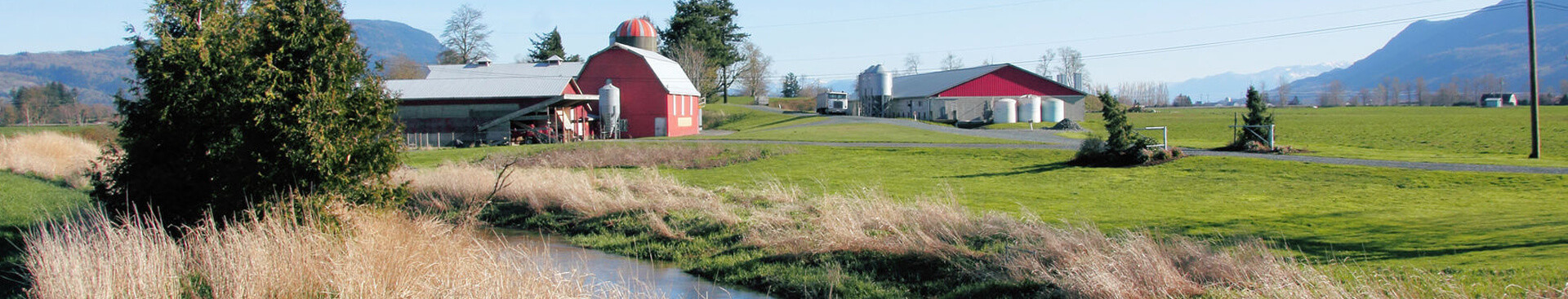 Red barn and farmhouse located beside a stream