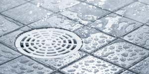 Close-up of a drain in a grey tiled shower
