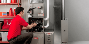 Man repairing a Bryant furnace in a mechanical room
