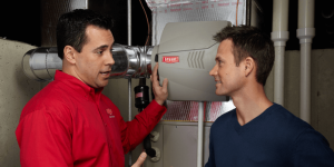 Repairperson explaining a humidifier system to a homeowner