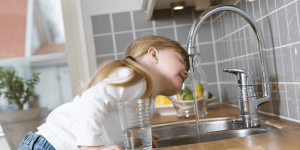 A young girl drinking from a kitchen tap
